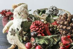 Christmas vintage decorations with snowman. A Christmas basket filled with cherries, pines, green and red decorations and snowman Royalty Free Stock Photography