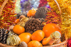 Christmas basket with fruit, pine cones and a bottle of wine Stock Photo