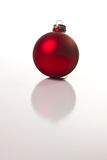 Christmas bauble. Red Christmas bauble or ball reflecting on white background Royalty Free Stock Photography