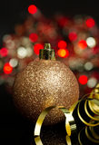 Christmas bauble. Christmas gold bauble with blurry lights background Stock Photos