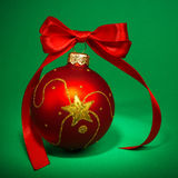 Christmas bauble. Red Christmas bauble with ribbon, green background Stock Images