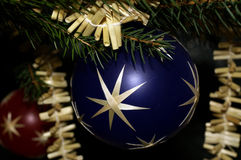 Christmas bauble. Closeup of blue Christmas bauble with decorated tree in background Royalty Free Stock Images