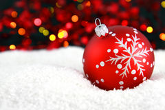 Christmas bauble. In snow with blurred lights in the background Stock Image