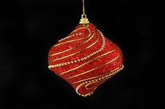 Christmas bauble against black. Red and gold Christmas bauble isolated against black royalty free stock images