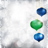 Christmas bauble background blue and green on silver. Christmas bauble background on glowing silver Royalty Free Stock Images