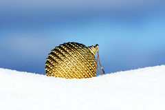 Christmas bauble on beautiful background. Golden christmas ball in snow Royalty Free Stock Images