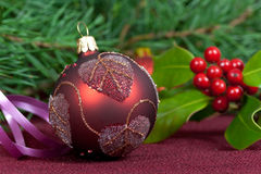A Christmas  bauble on dark,with holly Royalty Free Stock Photos