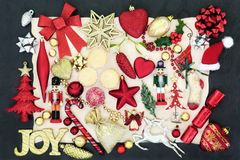Christmas Bauble Decorations. With gold joy sign, mince pies, holly, fir, mistletoe and foil wrapped chocolates on parchment paper on slate background Royalty Free Stock Image