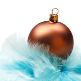 Christmas bauble in feathers nest. Decorative christmas bauble with blue feathers on white background Stock Photo