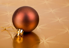 Christmas bauble on a golden background Stock Photos