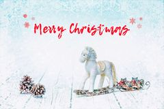 Christmas bauble horse and fir cones on white wooden background stock image