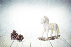 Christmas bauble horse and fir cones on white wooden background royalty free stock image