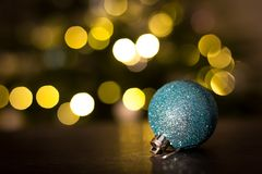 Christmas bauble with Christmas lights. In background Stock Images