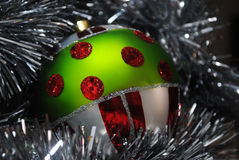 Christmas bauble nesting in silver tinsel 8. Green, red, white and silver Christmas bauble nesting in silver tinsel Royalty Free Stock Photo