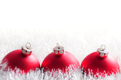 Christmas bauble postcard. Row of three red baubles in shiny white tinsel and copy space Stock Photography