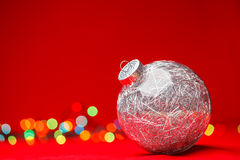 Christmas bauble on red background. Transparent Christmas bauble filled with silver tinsel on red background with blurred christmas lights Royalty Free Stock Images
