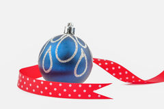 Christmas bauble with red dotted ribbon isolated on white.  Royalty Free Stock Photos