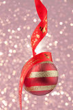 Christmas bauble with red ribbon on confetti background.  Royalty Free Stock Photos