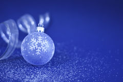 Christmas Bauble and Ribbon. A blue Christmas Bauble with silver Ribbon on snow sprinkled surface Royalty Free Stock Photo