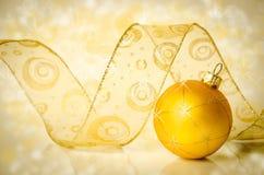 Christmas bauble and ribbon. Golden Christmas ball and ribbon Royalty Free Stock Photography
