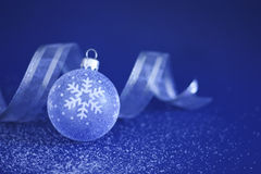 Christmas Bauble and Ribbon on Snow. A Christmas Bauble and Ribbon on snow with blue background Stock Photography
