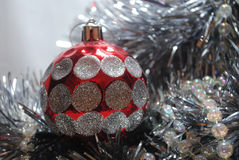 Christmas bauble 11. Silver and red Christmas baubles  sitting in silver tinsel and red beads Royalty Free Stock Photography