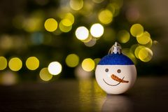 Christmas bauble snowman. And Christmas lights Royalty Free Stock Images