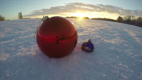 Christmas bauble on snowy december field and sunset light, time lapse 4K stock video footage