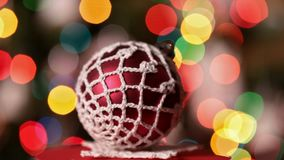 Christmas bauble spinning and sliding in front of xmas tree stock video