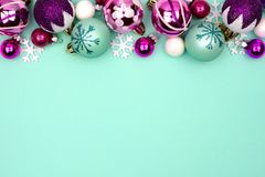 Christmas bauble top border on a turquoise background Royalty Free Stock Image