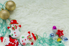 Christmas bauble on white fur and colorful lights Stock Photos