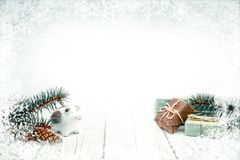Christmas baublepig, gift boxes and fir cones on white wooden background royalty free stock image