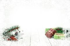 Christmas baublepig, gift boxes and fir cones on white wooden background royalty free stock photos