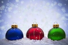 Christmas Baubles. Colored Christmas baubles in the snow with snowflakes Stock Photos