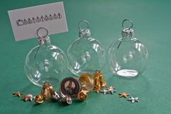 Christmas Baubles. Clear glass baubles bearing a christmas message with ribbons Royalty Free Stock Image