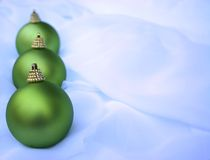 Christmas baubles. Row of three green Christmas bauble ornaments on light colored chiffon fabric with copy space Stock Photo