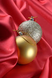 Christmas baubles. On a red silk fabric background Stock Photos