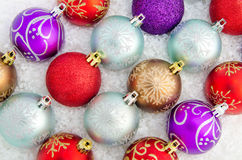 Christmas baubles. A group of Christma baubles resting in snow Stock Photo