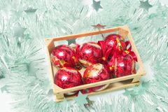 Christmas Baubles. Box of Christmas Baubles on Tinsels Royalty Free Stock Photography