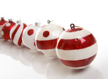 Christmas Baubles. A selection of red and white Christmas baubles on a white background.  Focus is to first bauble.  Space for copy Stock Photo