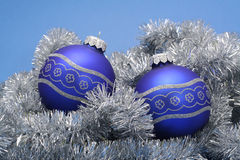 Christmas baubles. Blue christmas baubles on silver chain and blue background stock images