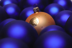 Christmas baubles. One golden christmal ball in a group of blue christmas balls Stock Image
