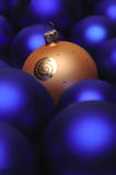 Christmas baubles. One golden christmal ball in a group of blue christmas balls Stock Photography