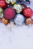 Christmas baubles. Coloured Christmas baubles in snow Stock Photo
