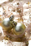 Christmas baubles background. Golden christmas baubles on glowing background with stars Royalty Free Stock Photo