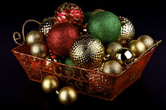 Christmas baubles in a basket. Red,gold and green Christmas baubles ornament in a basket on black background Stock Images