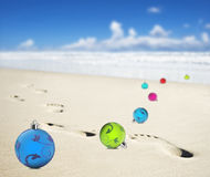 Christmas baubles on a beach with footprints. Of someone walking royalty free stock photography