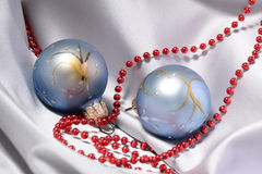 Christmas baubles and beads. Blue christmas baubles and red beads with silver satin in background Royalty Free Stock Images