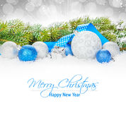 Christmas baubles and blue ribbon with snow fir tree Stock Images