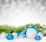 Christmas baubles and blue ribbon with snow fir tree. Over bokeh background with copy space Stock Images